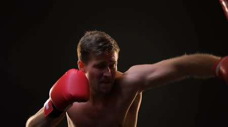 self injury : Professional boxer punching boxing bag, exhausted after training, motivation