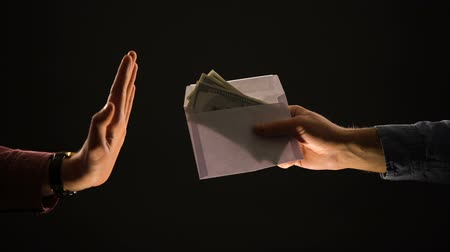 venality : Male giving envelope with dollars, person making stop gesture, refusing bribe Stock Footage