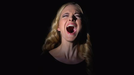 кричать : Blond woman shouting in darkness, releasing negative emotions, fighting stress