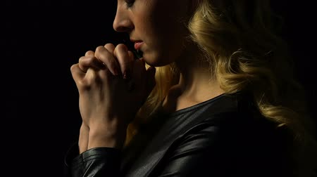 perguntando : Girl praying isolated on black, light falling on face as sign of forgiveness