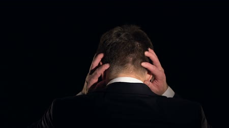 culpado : Man clutches head in despair, feeling hopelessness after failure, back view