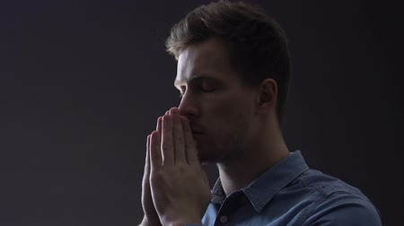обещание : Young man praying faithfully, looking for solution to difficult life problem Стоковые видеозаписи