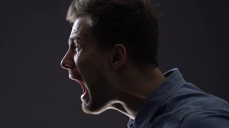 zuřivý : Frustrated man shouting in darkness, releasing negative emotion, fighting stress