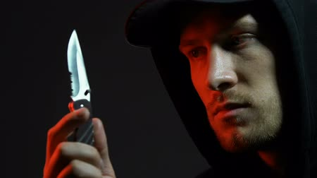 inbraak : Hooded man viewing folding knife, preparing for armed robbery, pickpocketing