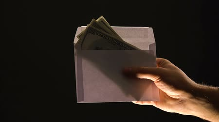 venality : Hand giving envelope with money isolated on black, corruption or illegal salary