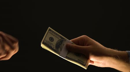 venality : Hand taking dollars on black background, dirty money concept, payment for crime Stock Footage