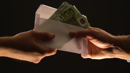 venality : Hand giving euros in envelope isolated on black, corruption or illegal salary