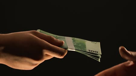 łapówka : Hand gives euros on black background, dirty money concept, payment for crime