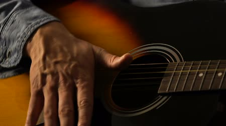 dizgi : Closeup of musician playing acoustic guitar, feeling rhythm and composing music
