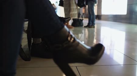 cancelado : Woman in high-heeled boots waiting flight in airport, business trip, closeup