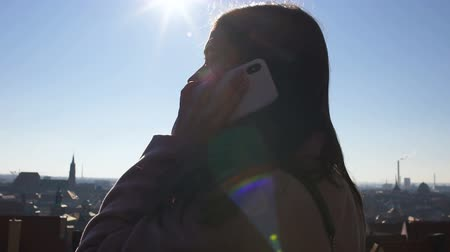 příznivý : Female calling from cell phone while watching European city from roof, roaming Dostupné videozáznamy