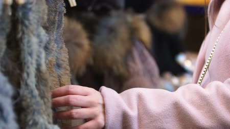 extinct species : Woman choosing fur coat in store, concept of killing animals for profit, closeup