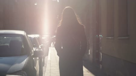 bizakodó : Female confidently walking down street towards sunlight to happy future, slow-mo