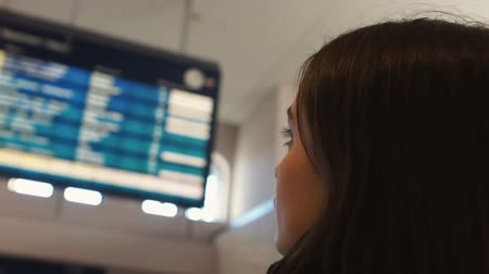 airport bus : Woman looking at airport display board, checking departure flight status closeup Stock Footage