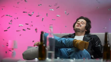 euforia : Happy drunk guy chilling out on couch at party, confetti falling down, relax Vídeos