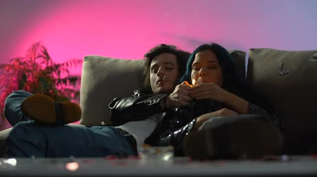 harmful habit : Drunk couple smoking cigarettes on nightclub couch, hangover girl feeling sick