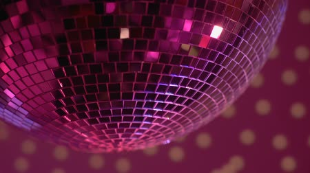 félrebeszél : Mirror disco ball rotating in nightclub lights, festive party atmosphere, fun