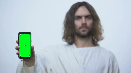 biblia : Man alike Jesus holding pre keyed smartphone, mobile bible application, online