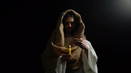 expiation : Messiah holding candle, praying for people sins expiation, belief and kindness