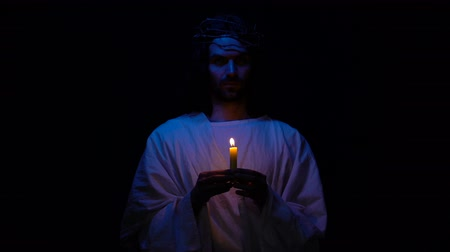 mortal : Christian saint in crown of thorns holding candle in darkness praying for people Vídeos