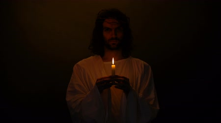 евангелие : Jesus in crown of thorns with candle praying for people, kindness sins expiation Стоковые видеозаписи
