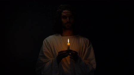 holy scripture : Holy man in crown of thorns holding candle in darkness Jesus before resurrection