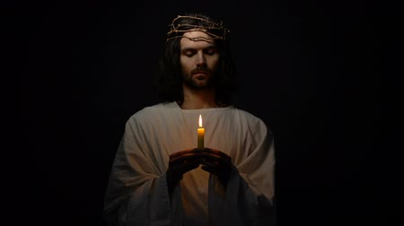 acreditar : Jesus Christ in crown of thorns holding candle and praying for god blessing hope