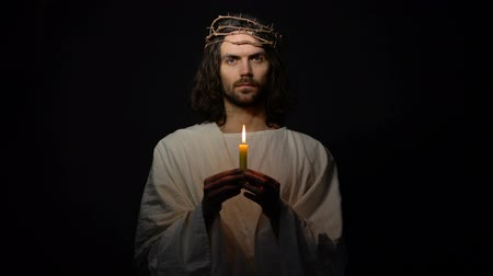 ukřižování : Male alike Jesus in crown of thorns blowing on candle, mortal people sins, god