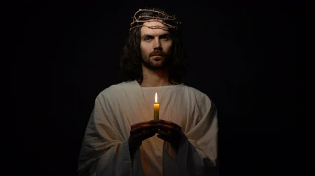 mortal : Saint in crown of thorns holding candle and looking to camera christian religion