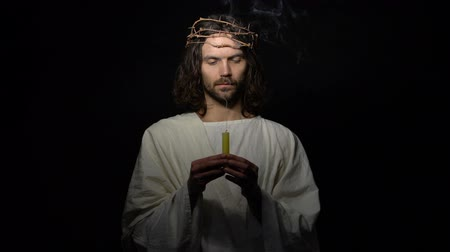 mortal : Jesus in crown of thorns holding smoking candle, disappearing in darkness, death Vídeos