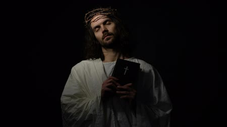 holy scripture : Jesus Christ with closed eyes in crown of thorns holding bible, spirit of god