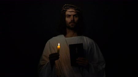 acreditar : Saint in crown of thorns holding candle and holy bible, christian faith in god