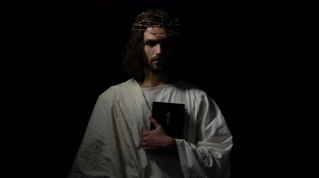 evangélium : Man in crown of thorns holding bible looking directly, Jesus before crucifixion Stock mozgókép