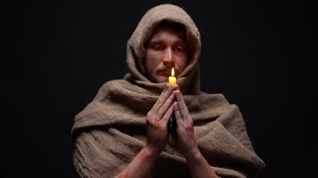 bibliai : Early christian in robe praying and holding burning candle, belief in god Stock mozgókép