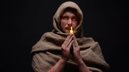 acreditar : Poor sick man in robe holding candle and praying god, asking for help.