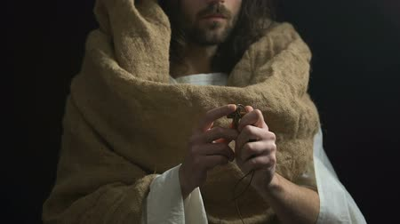 holy scripture : Jesus in robe showing Christian cross, crucifixion symbol, dark background