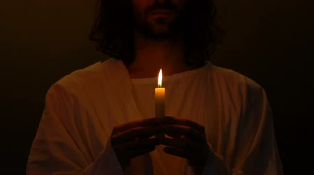 věčnost : Jesus Christ holding burning candle in darkness, saint symbol of christian pray