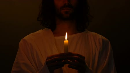 jewish prayer : Jesus Christ with burning candle standing in darkness, bringing hope and faith