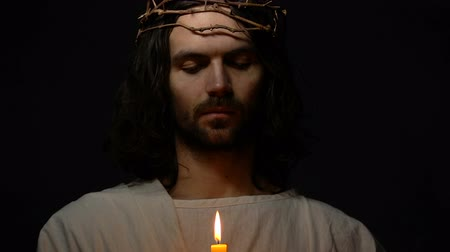 ukřižování : Jesus in crown of thorns holding votive candle, saving grace, religious sign Dostupné videozáznamy