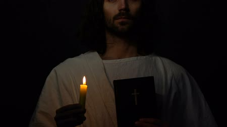 bible black : Jesus Christ in crown of thorns holding holy bible and burning candle, prophet