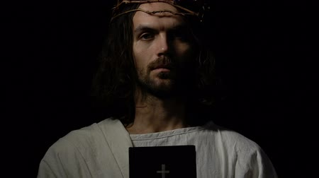 örök : Jesus in crown of thorns holding bible near heart, faith and belief concept