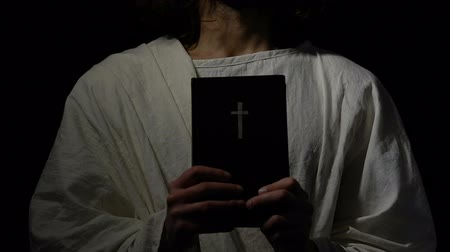 crucified : Religious person in robe holding holy bible near heart, Christian church, faith