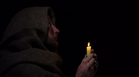 ümitsizlik : Poor sick beggar holding burning candle and praying to heaven, confession Stok Video