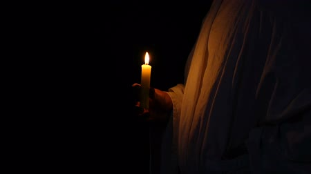 crucified : Man in robe holding burning candle against dark background, religious cult