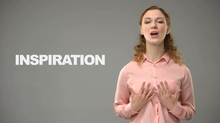 symbolic : Woman saying inspiration in sign language, text on background, communication Stock Footage
