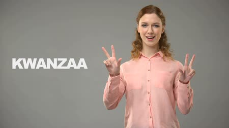 ortografia : Deaf lady saying kwanzaa in sign language, text on background, communication
