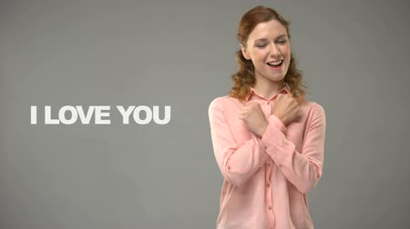 ortografia : Deaf woman saying love you in sign language, text on background communication