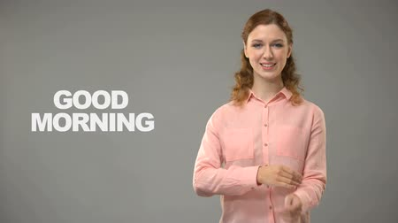 ortografia : Deaf lady saying good morning in sign language, text on background communication Stock Footage