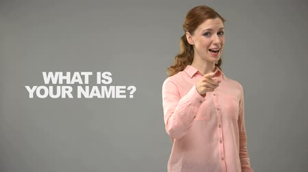 nomeação : Lady asking what is your name in asl, text on background, communication for deaf Stock Footage