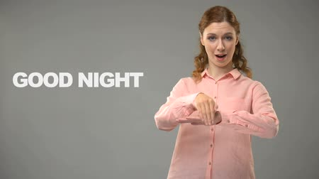 кулак : Deaf woman saying good night in asl, text on background, communication for deaf
